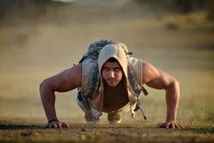 Idrotts- öva för ung man som är utomhus- på dammigt fält arkivbild