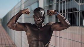 Idrotts- afrikansk amerikanman med en kal torso som utomhus poserar shower hans muskler Svart man som poserar nära stadion arkivfilmer