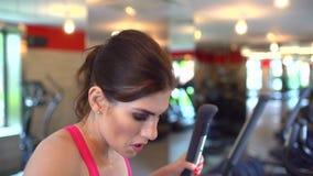 Idrotts- attraktiv caucasian ung kvinna som gör cardio övning i idrottshall Konditionflicka, sportwoman i rosa färgöverkant på at arkivfilmer