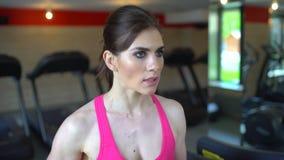 Idrotts- attraktiv caucasian ung kvinna som gör cardio övning i idrottshall Konditionflickan, sportwoman i rosa färger överträffa lager videofilmer
