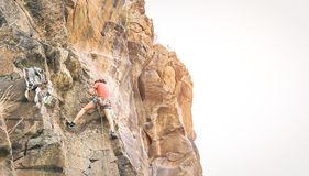 Idrotts- clambing för man vaggar väggen på solnedgången - klättraren som utför på ett kanjonberg - begreppet av sporten och den e royaltyfria bilder