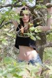 Idrotts- flicka med den plana buken som hänger från filial av trädet Arkivfoto