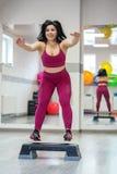 Idrotts- flicka som hoppar på gradvist i idrottshallen Övningsmuskel Begreppet av sportar, en sund livsstil, förlorande vikt arkivbilder