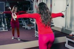 Idrotts- flicka som kopplas in i idrottshallen på simulatorn sportkondition och tyngdlyftning kvinnan ser in i av spegeln royaltyfri fotografi