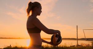 Idrotts- flicka som spelar hopp för strandvolleyboll i luften och slagen bollen över det netto på en härlig sommarafton lager videofilmer