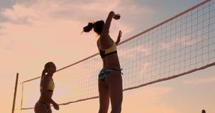 Idrotts- flicka som spelar hopp för strandvolleyboll i luften och slagen bollen över det netto på en härlig sommarafton arkivfilmer