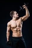 Idrotts- grabb för perfekt passform som poserar med skivstångplattan i idrottshall, perfekt latmuskel, skuldror, biceps, triceps  Arkivbild