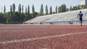 Idrotts- grabb som kör snabbt förgångna ställningar på stadion som förbereder sig för konkurrens stock video