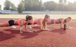 Idrotts- grupp av kvinnor som utbildar på en solig dag som gör plankövning i stadion Royaltyfri Fotografi