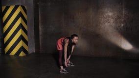 Idrotts- härlig kvinna som gör övningar i idrottshallen, idrottshallutbildningsrutin lager videofilmer