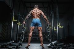 Idrotts- kroppsbyggare för pumpad man med kedjan i idrottshall tillbaka sikt arkivfoto