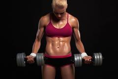 Idrotts- kroppsbyggarekvinna med hantlar härlig blond flicka med muskler royaltyfri fotografi