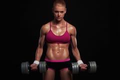 Idrotts- kroppsbyggarekvinna med hantlar härlig blond flicka med muskler royaltyfri foto