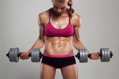 Idrotts- kroppsbyggarekvinna med hantlar härlig blond flicka med muskler royaltyfri bild