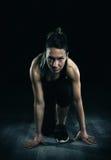 Idrotts- kvinna som är klar till överkörd mörk bakgrund Arkivfoto