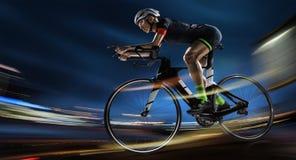Idrotts- kvinna som cyklar vägcykeln i aftonen arkivbild