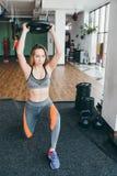 Idrotts- kvinna som gör övningar i idrottshallen Fotografering för Bildbyråer