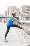 Idrotts- kvinna som gör elasticiteter i gatan royaltyfri fotografi