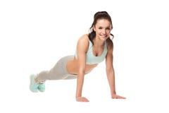 Idrotts- kvinna som gör push-UPS på en vit bakgrund Konditionmodell med en härlig idrotts- kropp Arkivfoto