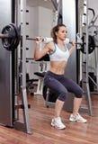 Idrotts- kvinna som gör squats på idrottshallen Arkivbilder