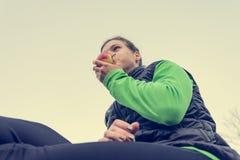 Idrotts- kvinna som har ett sunt fruktmellanmål under utomhus- övning royaltyfri foto