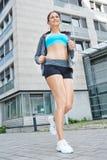Idrotts- kvinna som joggar i staden Arkivfoto