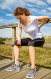 Idrotts- kvinna som tillbaka trycker på hennes muskler vid skada royaltyfri bild