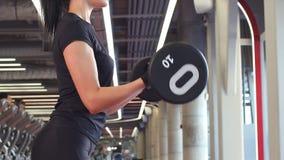 Idrotts- kvinna som upp pumpar muscules med skivstången arkivfilmer