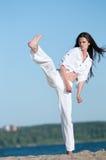 Idrotts- kvinna som utför en kick Arkivbild
