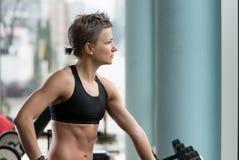 Idrotts- kvinnagenomkörare med vikter i idrottshallen Arkivfoton
