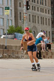 Idrotts- kvinnaRollerblades på den stads- gatan royaltyfri bild