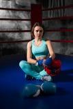 Idrotts- kvinnlig boxare som sitter nära liggande boxninghandskar och helme Arkivfoton