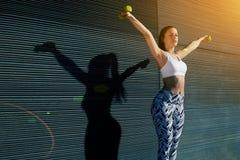 Idrotts- kvinnlig med det perfekta diagramet som får hennes armar i stor form, medan lyfta vikter Arkivbild