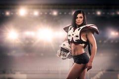 Idrotts- kvinnlig som kläs som en amerikansk fotbollsspelare Verklig likformig, hjälm, block, boll royaltyfri fotografi