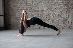 Idrotts- kvinnligt görande högt vridningutfall för yoga royaltyfri fotografi