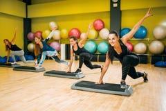 Idrotts- kvinnor på aerobisk genomkörare för moment inomhus arkivbild