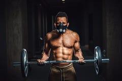 Idrotts- man för afrikansk amerikan i maskeringen som ser kameran och lyfter skivstången på biceps Övning för biceps med skivstån Fotografering för Bildbyråer