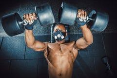 Idrotts- man för afrikansk amerikan i maskeringslyftande hantlar och arbete på hans bröstkorgsikt från över svart man i idrottsha Arkivfoton