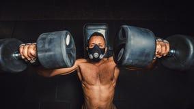Idrotts- man för afrikansk amerikan i maskeringslyftande hantlar och arbete på hans bröstkorgsikt från över svart man i idrottsha Royaltyfri Fotografi