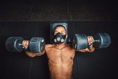 Idrotts- man för afrikansk amerikan i maskeringslyftande hantlar och arbete på hans bröstkorgsikt från över svart man i idrottsha Royaltyfri Foto