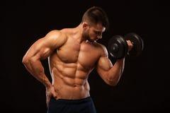 Idrotts- man för stilig makt med hanteln som säkert framåtriktat ser Stark kroppsbyggare med sex packe, perfekt abs Arkivfoton