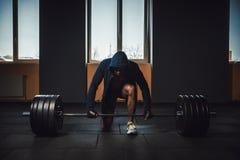Idrotts- man i omslag med en huv som väntar och förbereder sig, innan att lyfta den tunga skivstången Kondition, sport, utbildnin Royaltyfri Foto