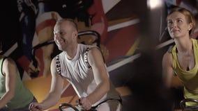 Idrotts- man och sportiga kvinnor som utarbetar tillsammans genom att använda stationära cyklar