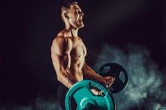 Idrotts- man som gör övningar med hantlar på biceps Foto av den starka mannen med den nakna torson på mörk bakgrund Arkivbild