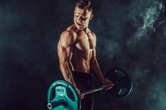 Idrotts- man som gör övningar med hantlar på biceps Foto av den starka mannen med den nakna torson på mörk bakgrund Royaltyfri Foto