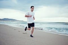 Idrotts- manlig joggerspring på stranden Royaltyfri Bild