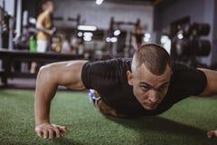 Idrotts- muskulös man som övar på idrottshallen royaltyfri foto