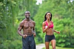 Idrotts- och färdiga afrikansk amerikanpar - jogga i en parkera Royaltyfri Bild