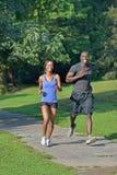 Idrotts- och färdiga afrikansk amerikanpar - jogga i en parkera Arkivbild