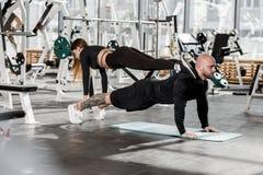 Idrotts- par som gör svår sportövning var flickan står i plankan på en man, som står i plankan in royaltyfria foton